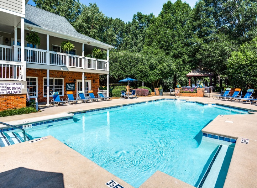 View of Pool Area, Showing Outdoor Furniture, Loungers, and Picnic Areas at Plantations at Haywood Apartments